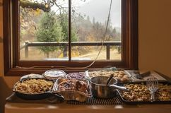 Thanksgiving dinner served in pans on table by window looking outside of cabin in the woods on rainy day stock photography