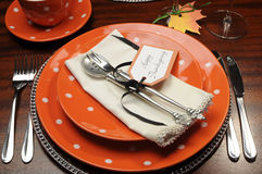 Thanksgiving dinner table place setting with orange plates and Happy Thanksgiving tag. Beautiful Autumn Fall theme Thanksgiving dinner table place setting with royalty free stock photo