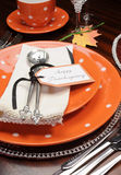 Thanksgiving dinner table place setting with orange plates and Happy Thanksgiving tag - vertical. Royalty Free Stock Photography
