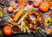 Thanksgiving dinner table with Roasted whole turkey ,sauce with grilled autumn vegetables,corn ,cutlery , decoration pumpkin, autu. Mn leaves and flowers stock photos