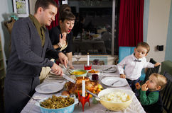 Thanksgiving Dinner Turkey Family. Dad carves the turkey while his young boys celebrate Thanksgiving dinner with their mom and dad stock images