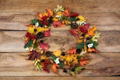 Thanksgiving door wreath with red maple, green and yellow oak leaves, viburnum, black berries, acorns, pine cones stock image