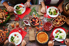 Thanksgiving feast. Above view of thanksgiving dinner and family eating at table royalty free stock photography