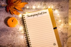 Free Thanksgiving Food Drive List Concept On Notebook Surrounded With Bright Leaves And Decorative Lights, Flat Lay Royalty Free Stock Photography - 130460197