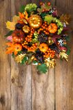Thanksgiving front door wreath with fall leaves. Thanksgiving front door wreath with pumpkins and autumn leaves. Fall greeting background with seasonal berries Royalty Free Stock Photography