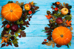 Thanksgiving greeting with leaves and pumpkin on blue wooden tab Stock Images