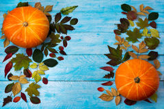 Thanksgiving greeting with pumpkin and autumn leaves on blue wood Royalty Free Stock Photo