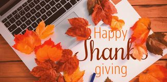 Composite image of thanksgiving greeting text. Thanksgiving greeting text against laptop coated of leaf Stock Photography