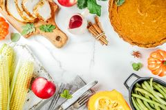 Thanksgiving holiday food. Thanksgiving holiday table with traditional festive food - turkey, pumpkin pie, pumpkins, green beans, cranberry sauce, corn, autumn royalty free stock photography
