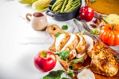 Thanksgiving holiday food. Thanksgiving holiday table with traditional festive food - turkey, pumpkin pie, pumpkins, green beans, cranberry sauce, corn, autumn royalty free stock images