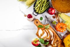 Thanksgiving holiday food. Thanksgiving holiday table with traditional festive food - turkey, pumpkin pie, pumpkins, green beans, cranberry sauce, corn, autumn royalty free stock photo