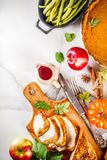 Thanksgiving holiday food. Thanksgiving holiday table with traditional festive food - turkey, pumpkin pie, pumpkins, green beans, cranberry sauce, corn, autumn royalty free stock image