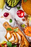 Thanksgiving holiday food. Thanksgiving holiday table with traditional festive food - turkey, pumpkin pie, pumpkins, green beans, cranberry sauce, corn, autumn stock images