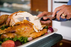 Thanksgiving: Man Carving Slices Of Roast Turkey For Dinner. Traditional Thanksgiving holiday in the USA, with family preparing turkey and gathering around the royalty free stock images
