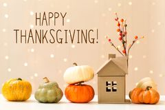 Thanksgiving message with pumpkins with a house. Thanksgiving message with collection of autumn pumpkins with a toy house stock image