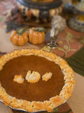Thanksgiving Pumpkin Pie. A Thanksgiving pumpkin pie decorated with fall leaves and turkey shaped pastry sitting on Thanksgiving decorated table Stock Image