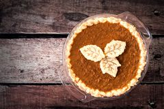 Thanksgiving pumpkin piPumpkin pie with leaf pastry toppings against rustic wood Stock Photography