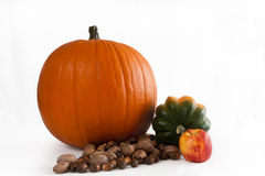 Thanksgiving Pumpkin. Pumpkin with squash, apple, pecans and acorns Stock Photography