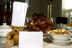 Thanksgiving Recipe. Table laden with Thanksgiving feast with a teddy bear wearing a chefs hat and holding a recipe card Royalty Free Stock Image