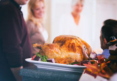 Thanksgiving: Roasted Turkey Rests On Counter While Family Talks Royalty Free Stock Photo
