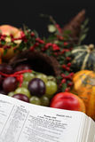 Thanksgiving Scripture and cornucopia. Bible open to Psalm 100 with thanksgiving text and cornucopia in background Stock Image