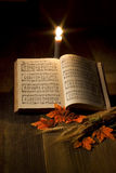 Thanksgiving Song. Thanksgiving hymnal on a table with a candle Royalty Free Stock Photography