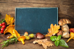 Thanksgiving still life with mushrooms, seasonal fruit and veget. Ables on wooden table with space for text.  Cooking concept Royalty Free Stock Image
