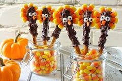 Thanksgiving turkey pretzel sticks with candy corn, still life. Cute Thanksgiving turkey pretzel sticks with candy corn, still life against a white brick stock photo