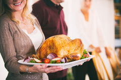 Thanksgiving: Woman Holding Platter With Roast Turkey And Garnish. Traditional Thanksgiving holiday in the USA, with family preparing turkey and gathering around