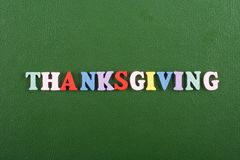 THANKSGIVING word on green background composed from colorful abc alphabet block wooden letters, copy space for ad text. Word on green background composed from stock images