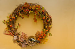 Thanksgiving Wreath. Autumn / Thanksgiving themed wreath of brown twigs, decorated with dry maple leaves, wheat, orange berries, an orange and green plaid bow Stock Photo