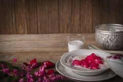 Thapthim krop, mock pomegranate seeds in coconut and syrup in the white bowl on the wood table there are flower, spoon, coconut royalty free stock image