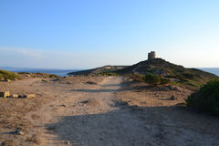 Tharros archeological site in Sardinia, Italy. Ancient landscape with a Spanish watchtower on the hill, and beautiful coastline at sunset stock image