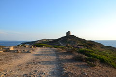 Tharros archeological site in Sardinia, Italy. Ancient landscape with a Spanish watchtower on the hill, and beautiful coastline at sunset stock photos