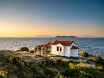 Thasos island at sunrise with blue waters and beautiful small white church greek style. Thasos or Thassos Island is a summer destination island in the Aegean royalty free stock photos