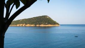 Η άποψη ματιών πουλιών ενός νησιού στα thassos Ελλάδα με το πορτοκάλι βγάζει φύλλα και ένα BOT στο midle της μπλε θάλασσας στοκ εικόνες
