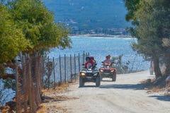 THASSOS, GRÉCIA - 5 de setembro de 2016 - turistas que montam o atv na estrada de terra na ilha de Thassos, Grécia Imagem de Stock