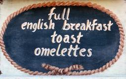 THASSOS, GRÉCIA 13 de setembro de 2015: Um sinal de madeira fora de um restaurante, café da manhã inglês completo, brinde, omelet imagens de stock