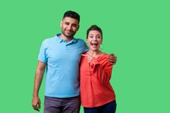 That`s Him! Portrait Of Happy Young Couple In Casual Wear Standing Together. Isolated On Green Background Stock Photos