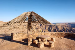 Thatch-roofed umbrella against canyon Stock Image