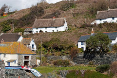 Cadgwith Cove Cottages. Thatch and slate roofed cottages cluster around and above the picturesqe Cornish cove at Cadgwith Stock Image