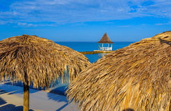 Thatch Umbrellas on Beach, Montego Bay Jamaica wedding gazebo on beach pier in background Stock Photo