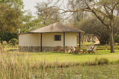 Thatched African house. A view across a grassy lawn to a small thatched house in Zambia, Africa Royalty Free Stock Image