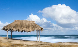 Thatched  bamboo hut on beach. Bamboo hut on a tropical beach with white puffy clouds in sky Royalty Free Stock Images