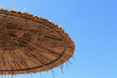 Thatched beach umbrella on clear blue sky background Royalty Free Stock Photography