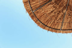 Thatched beach umbrella on clear blue sky background Royalty Free Stock Photos