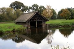 Thatched boathouse at River Avon bank, Warwick castle garden, England Royalty Free Stock Photography