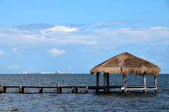 Thatched Cabana on Dock with Cancun on the Horizon Stock Image