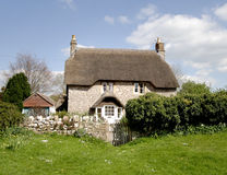 Thatched Cottage. A natural stone Thatched Village Cottage in rural England with a dry stone wall to the front Stock Photo