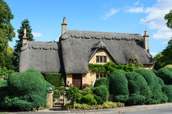 Thatched cottage with beautiful garden. An English thatched cottage built out of Cotswold stone with a beautiful hedge in the garden in Chipping Campden, the Stock Photography